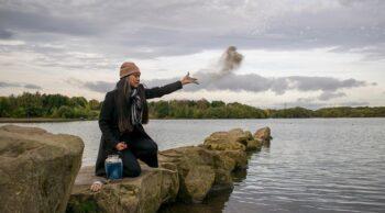 Na imagem vemos uma mulher jogar cinzas no mar. Entenda porque optar pela cremação!