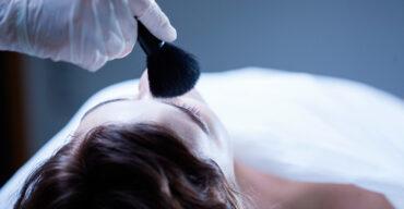 Profissional passa maquiagem nos olhos durante a preparação do corpo para o velório